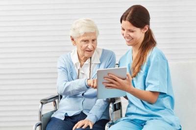 senior citizen in wheelchair learns from caregiver dealing with tablet